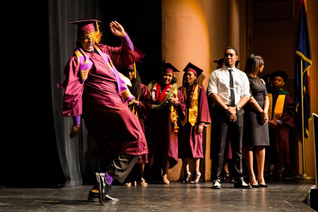 graduate dancing across stage