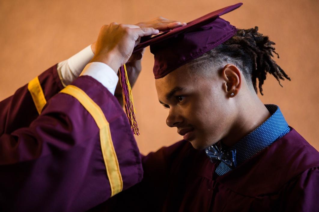 A student adjusts his graduation cap.