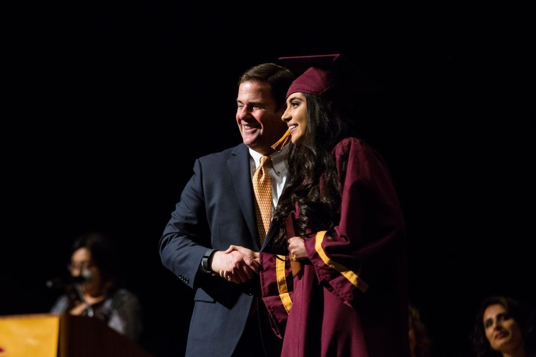 Arizona Gov. Doug Ducey poses with an ASU Prep graduate.