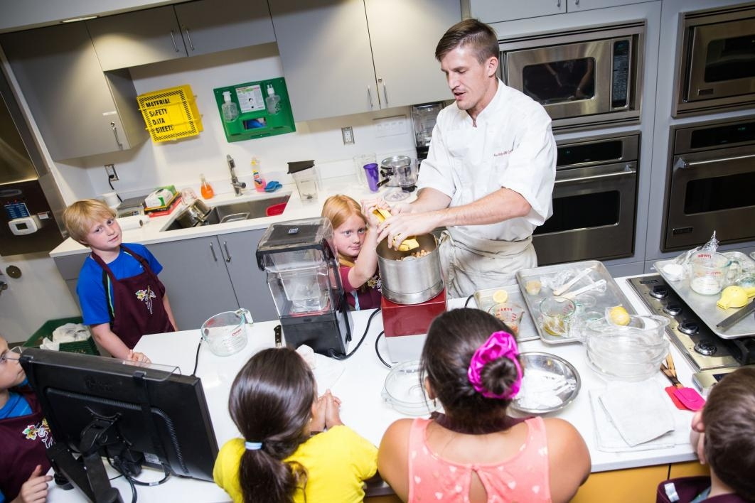 A chef teaches young students how to cook at Camp Crave