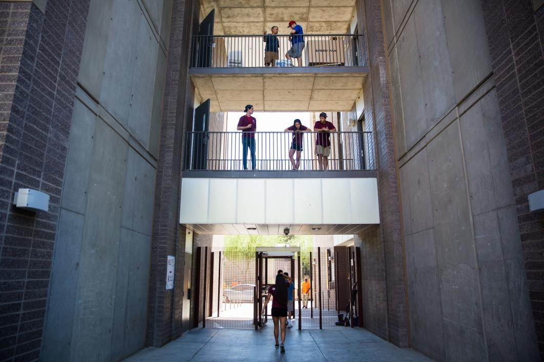 people standing on dorm balconies