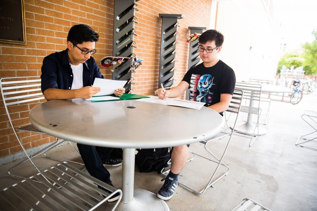 two students sitting outside at table