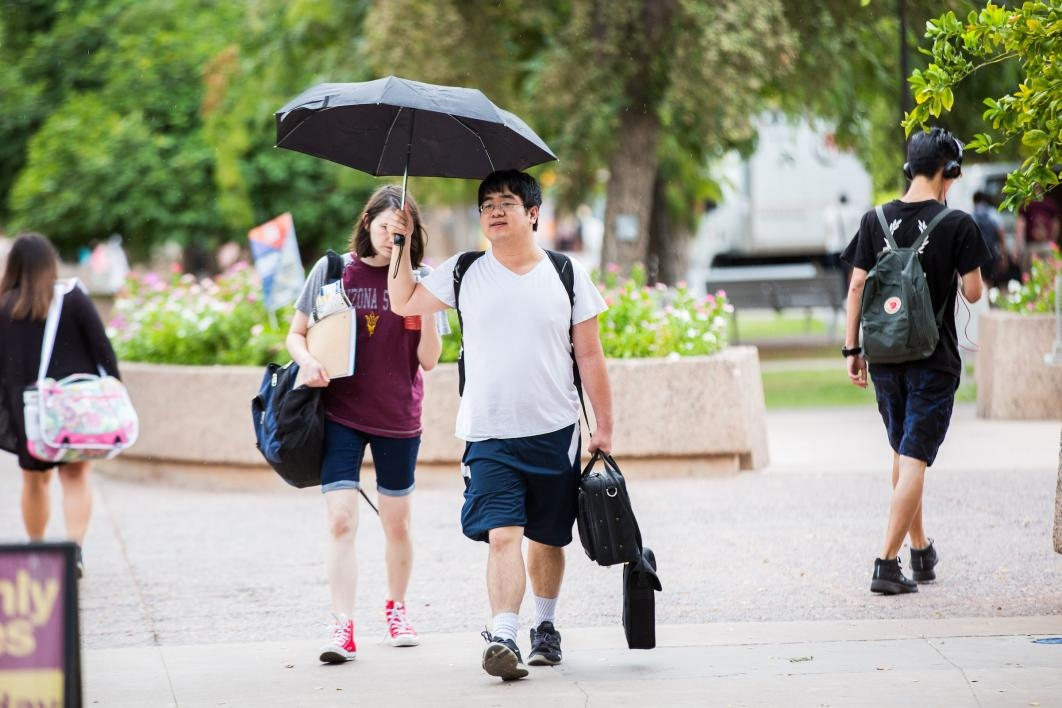 two students walking on campus carrying umbrella