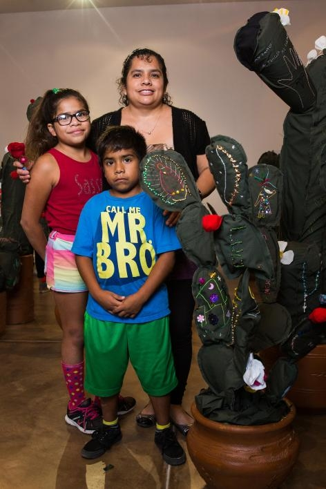 A family poses with a cloth cactus embroidered with their immigration story.