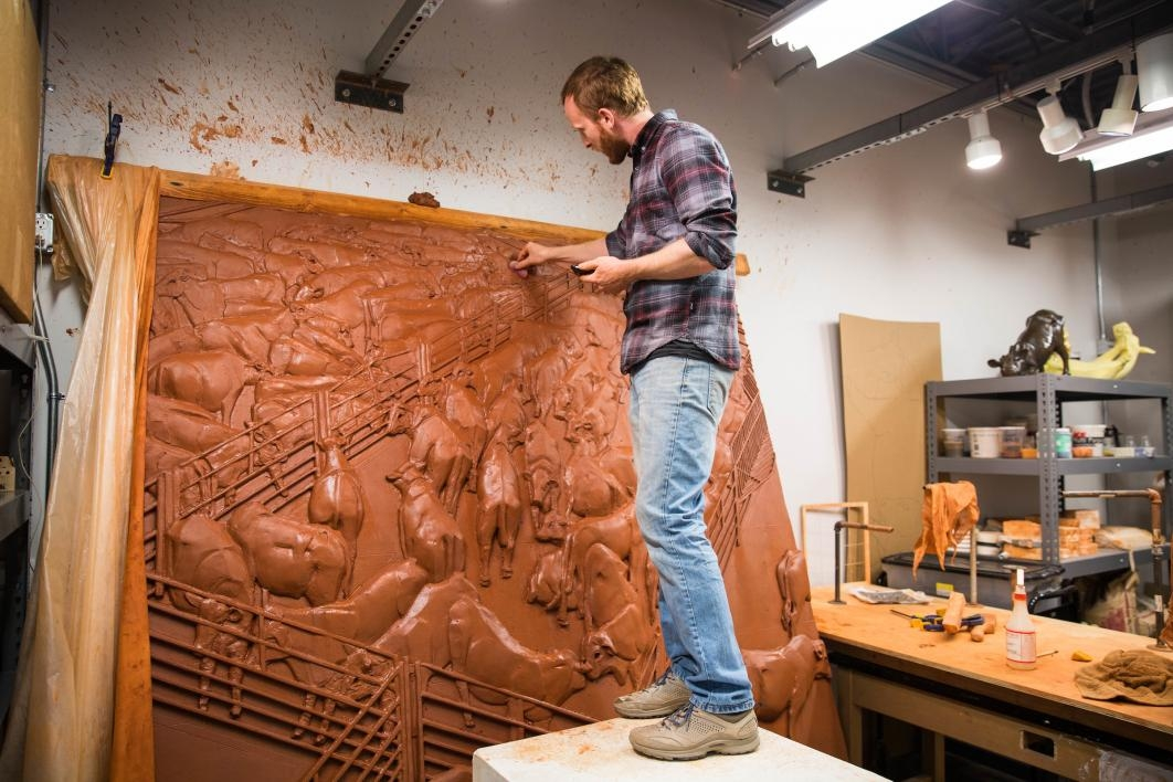 Artist Elliott Kayser works on a large-scale ceramic carving