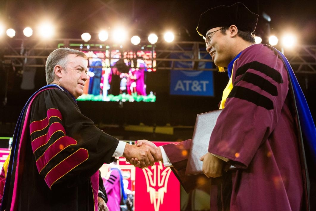 student shaking hands with ASU President
