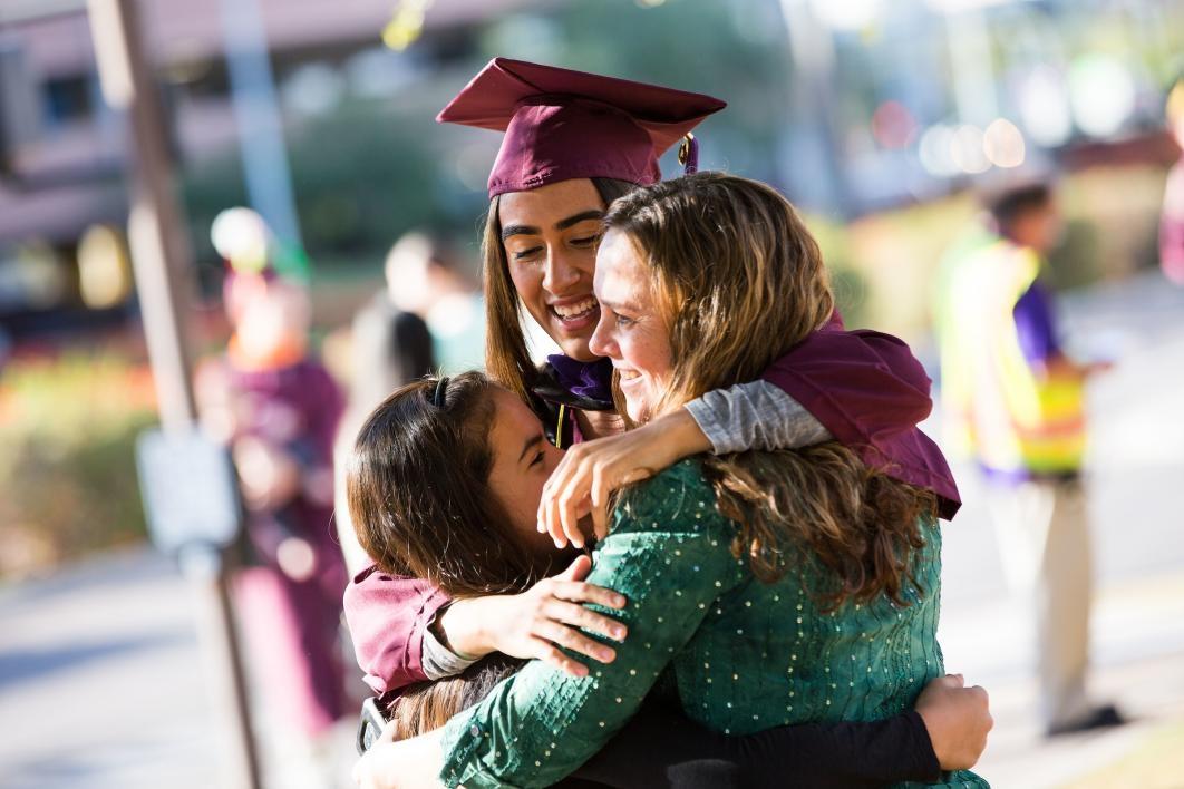 ASU graduate hugging friends