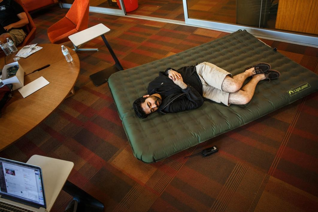 A staffer naps on an inflatable mattress during the hackathon