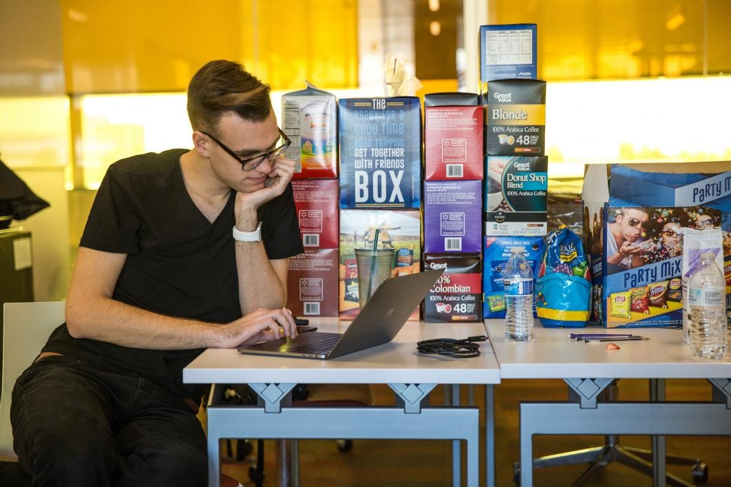 A man guards the snacks at the hackathon