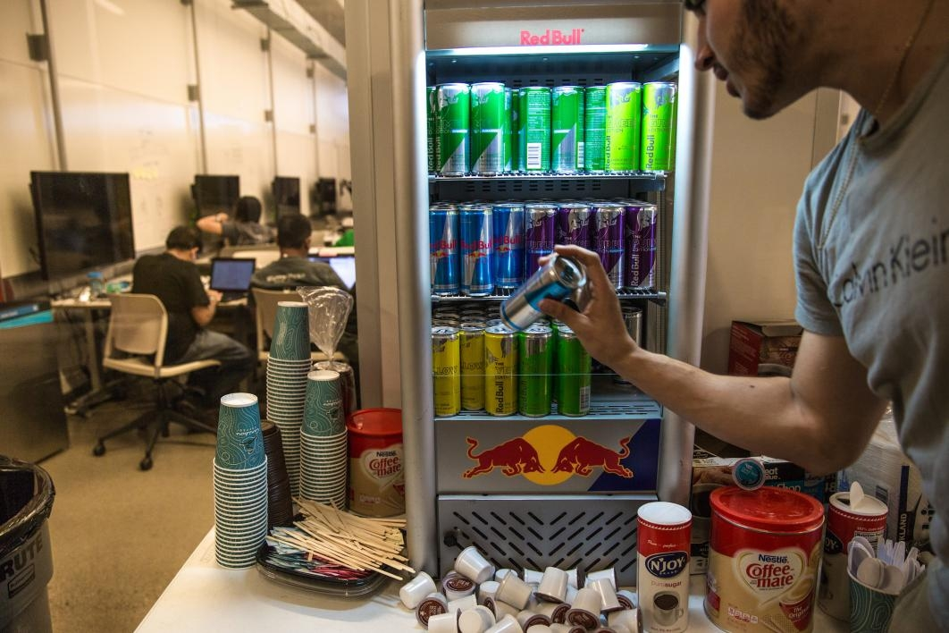 A student pulls a Red Bull out of a mini fridge at the hackathon