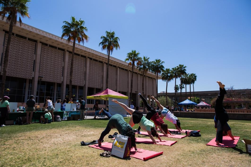 students practicing yoga on the lawn