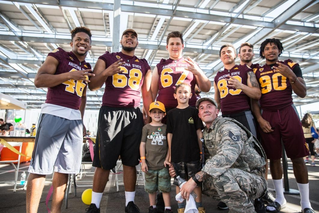 A soldier and his kids pose with ASU football players after the 2017 Pats Run