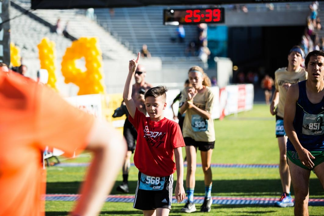 A boy is the first kid to cross the finish line at Pats Run