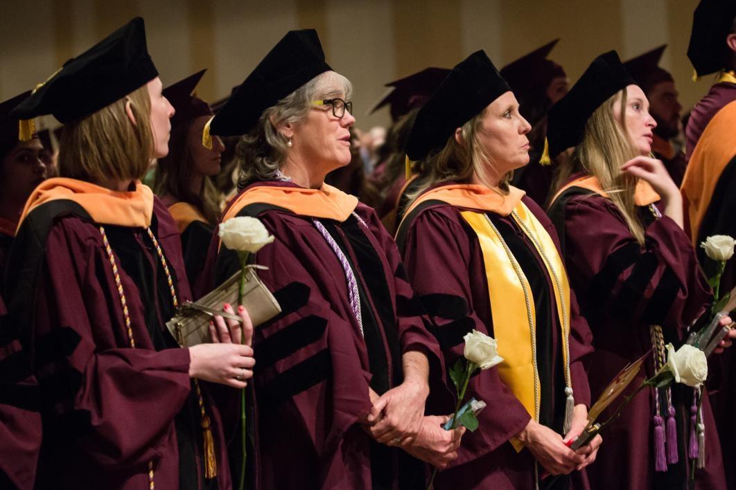 graduates holding roses