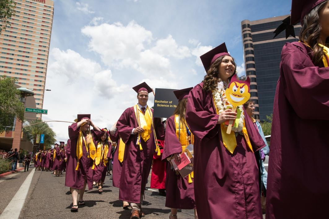 graduates walking down downtown street