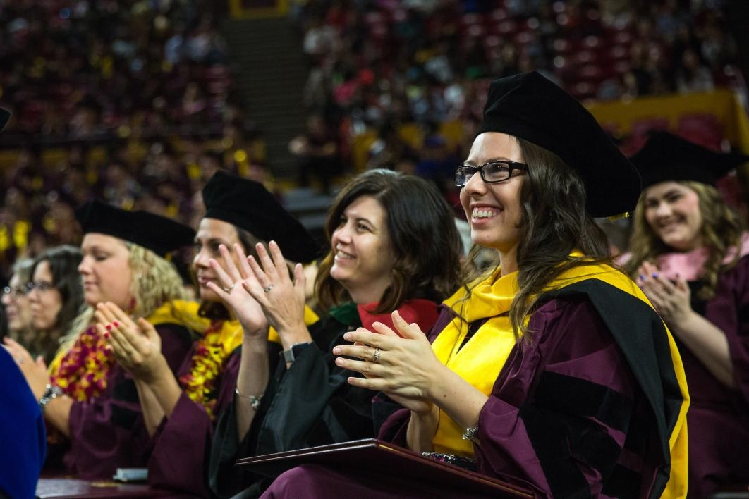 graduate clapping during ceremony