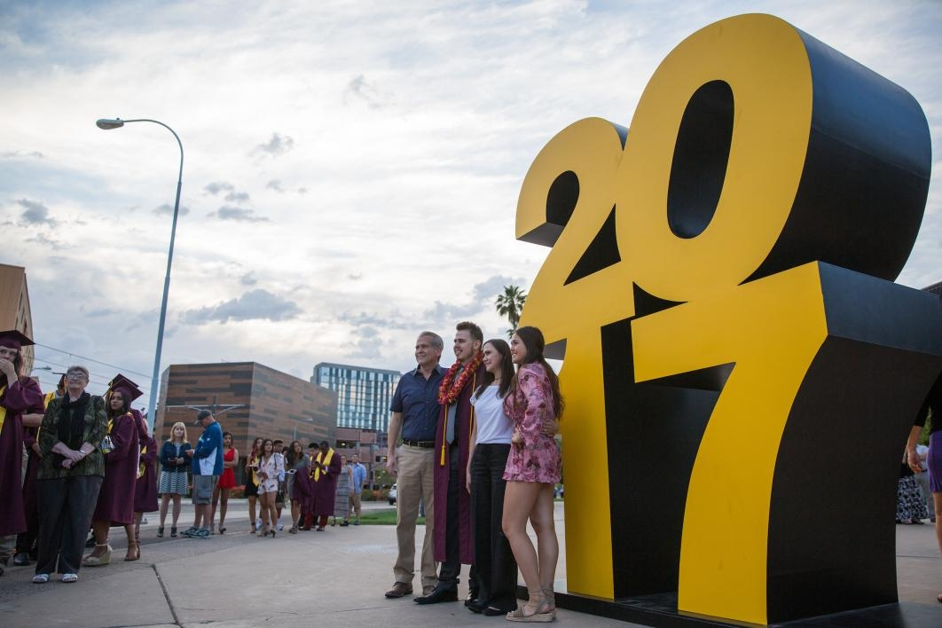 people standing in front of statue that says 2017