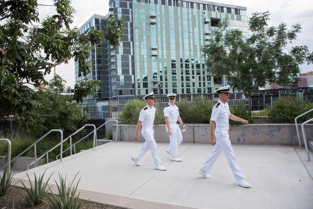 three people in uniform walking