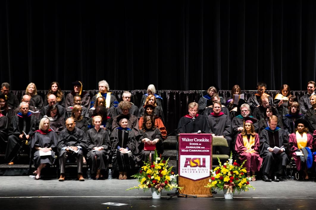 man speaking on stage with graduates behind him