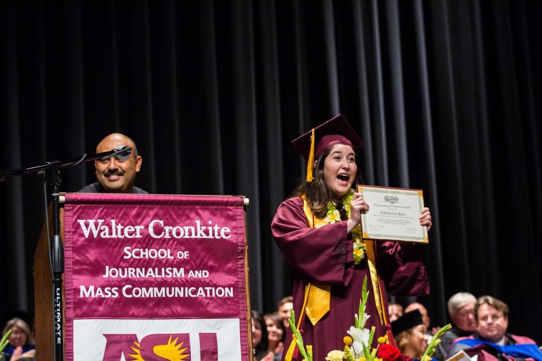 graduate holding up an award