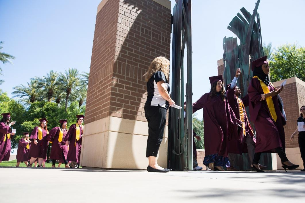 graduates passing through West campus gates