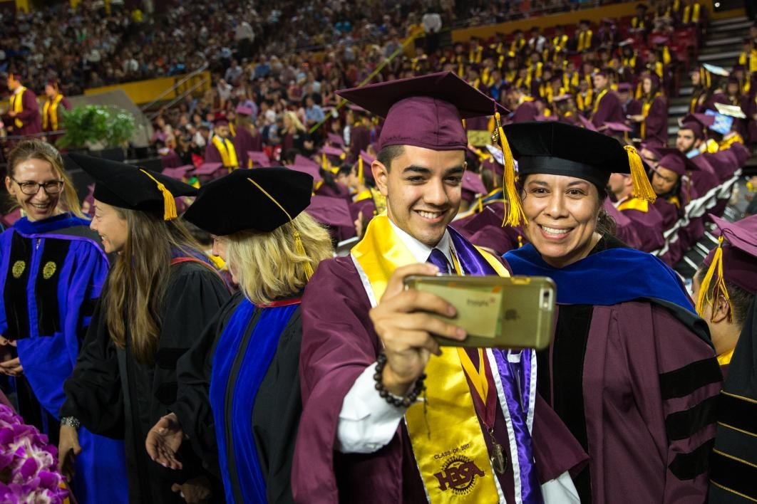 graduate and professor taking a photo