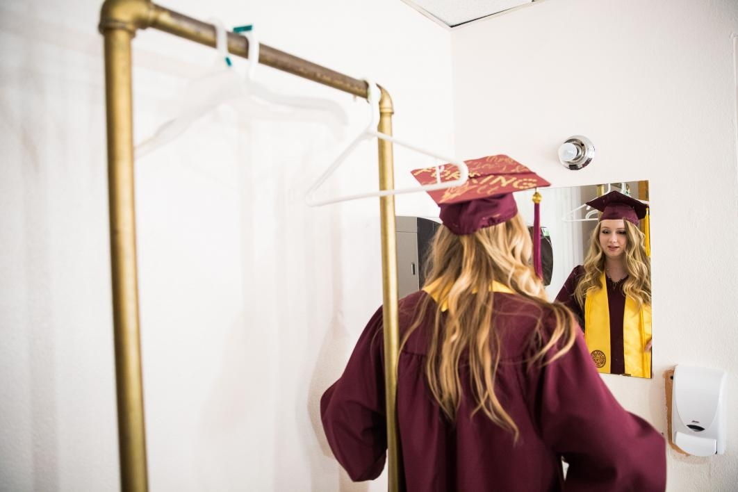 graduate looking in the mirror