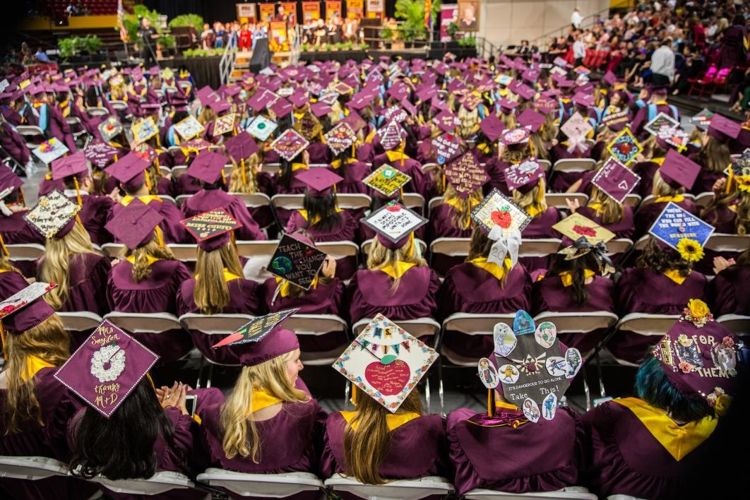 crowd of graduates with decorated caps