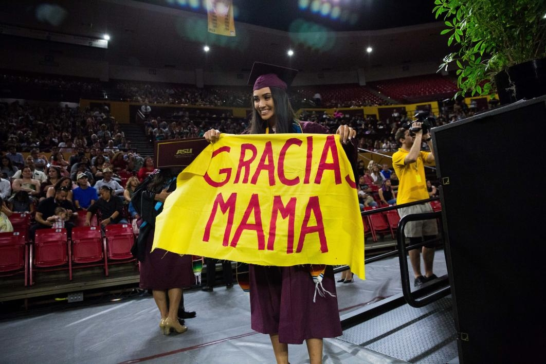 "grad holding sign that says ""Gracias Mama"""