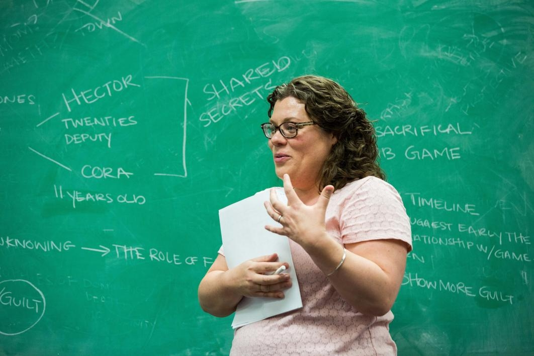 A woman stands at a chalkboard