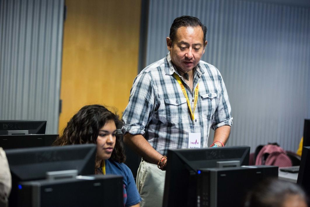 Indigenous Rhetoric coordinator and mentor Kyle Wilson works with high school student Alianna Pinon
