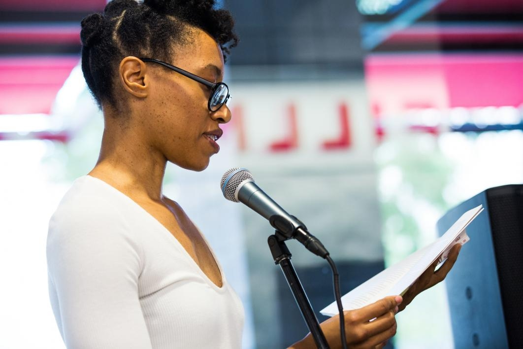A woman reads her writing at a workshop
