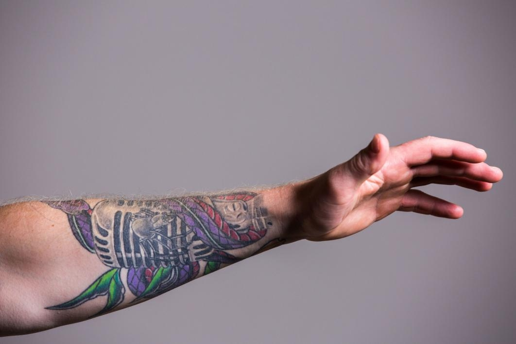forearm tattoo of a microphone and a spider