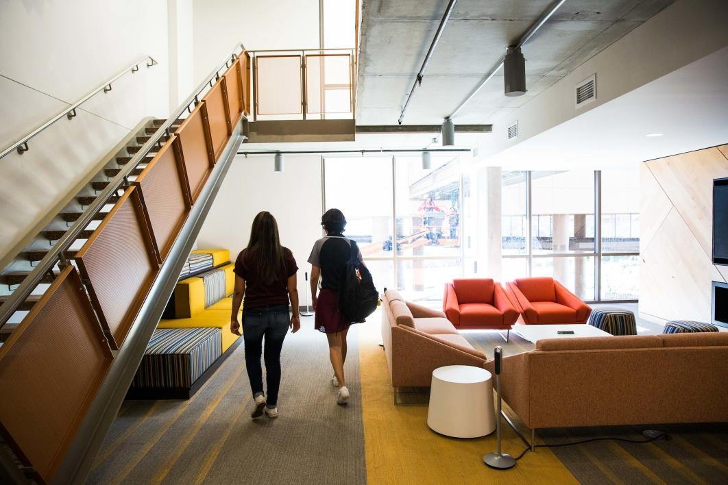 Students walk through a social area at Tooker House