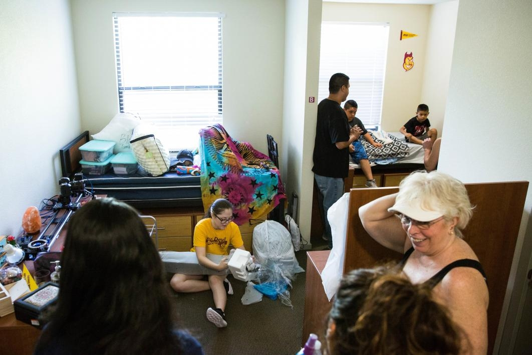 Families unpack in a dorm room