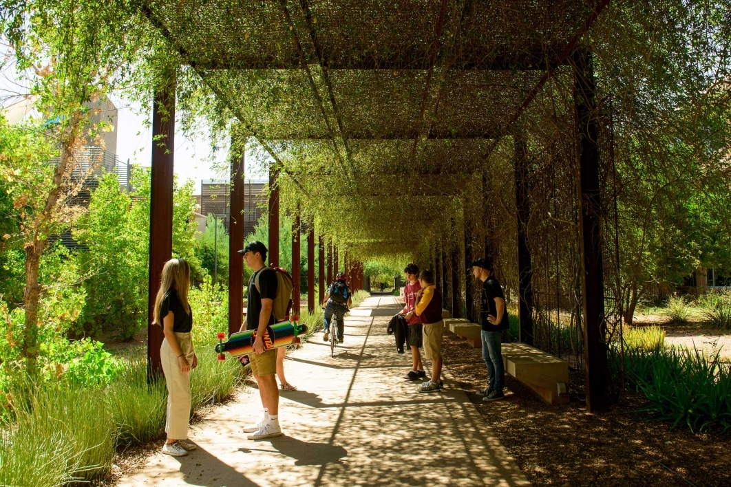 People gather beneath an outdoor arbor on the Polytechnic campus