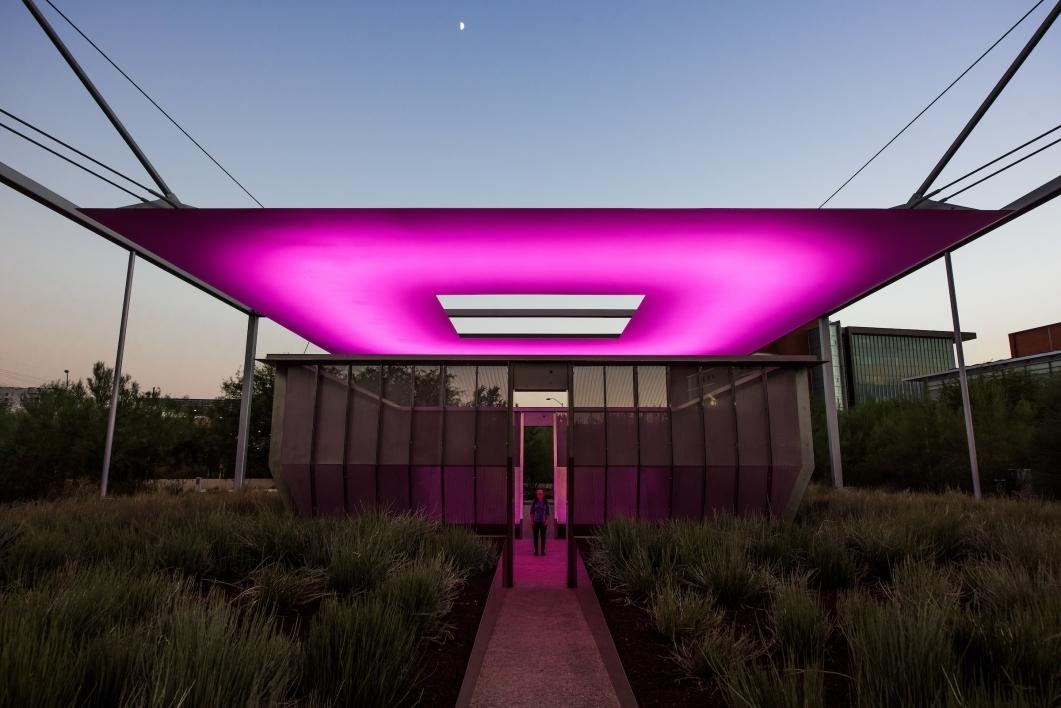 An outdoor art installation glows pinkish purple