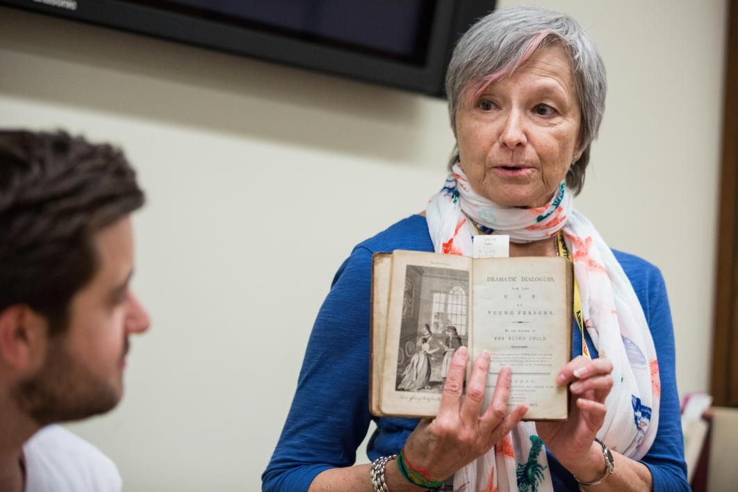 Child Drama collection archivist Katherine Krzys shares a historical book with students