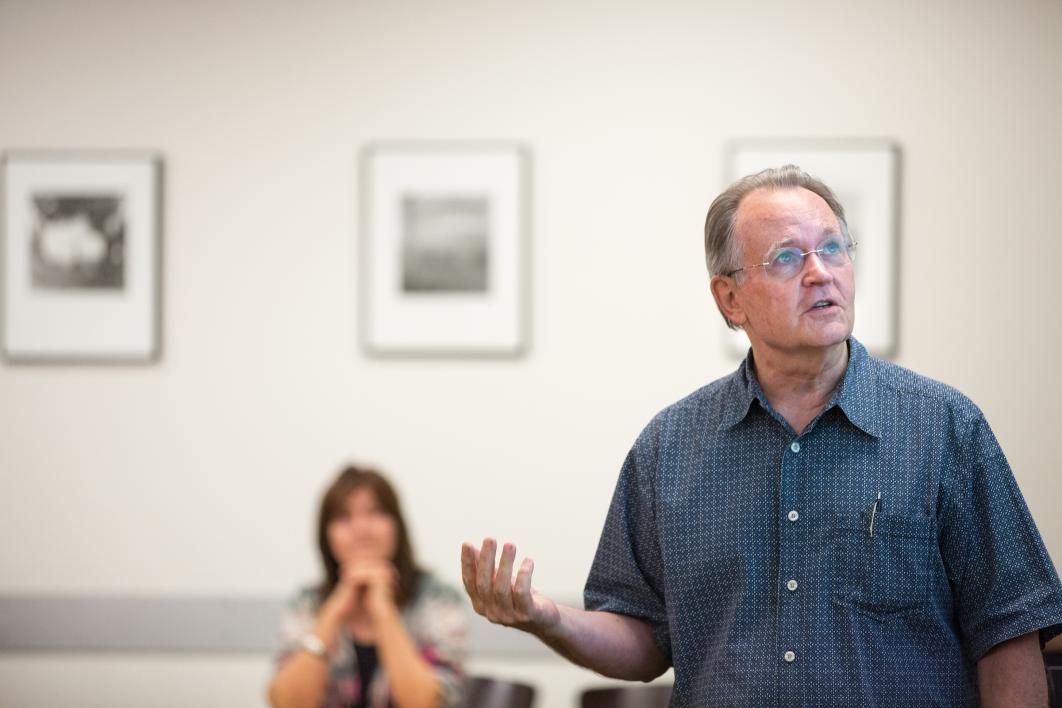 man giving lecture with woman in background