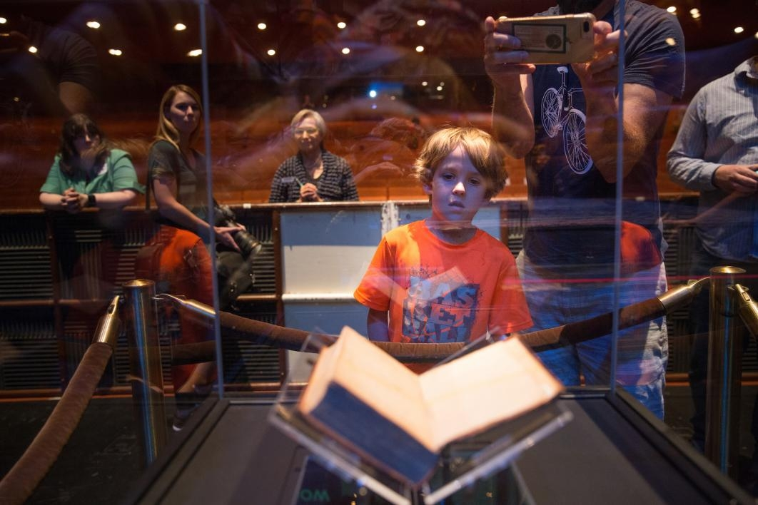 A boy looks at the Federalist Papers in a case at ASU Gammage