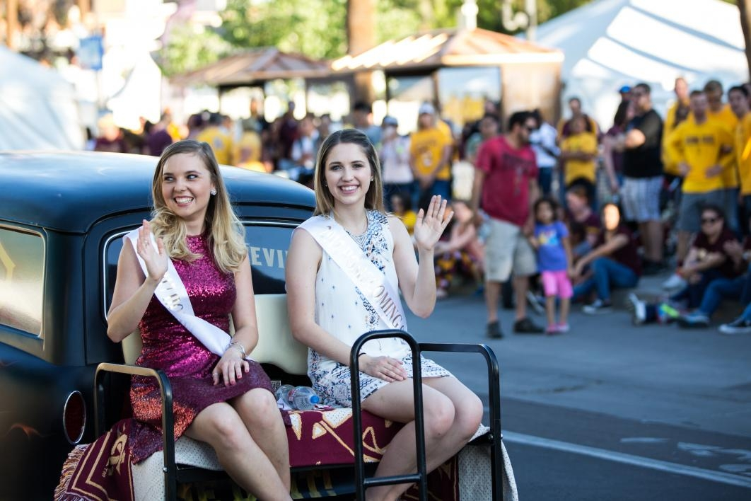 two women riding on car in parade