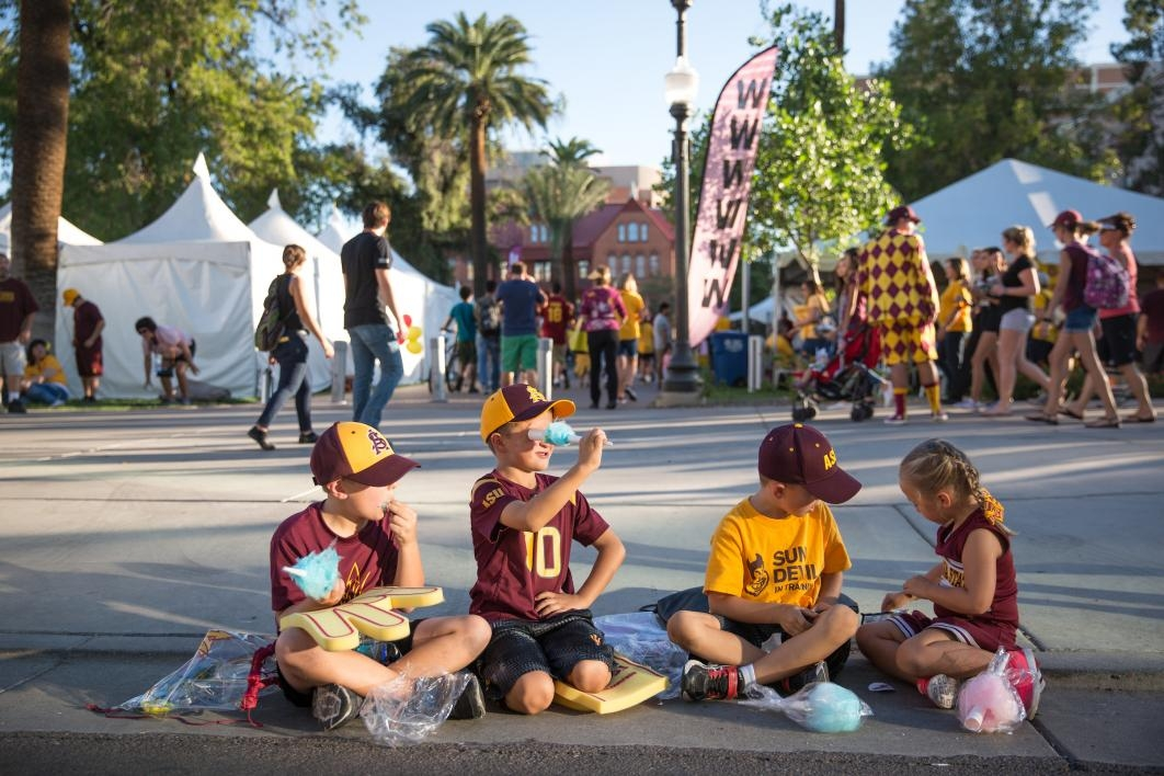 children sitting on sidewalk during parade