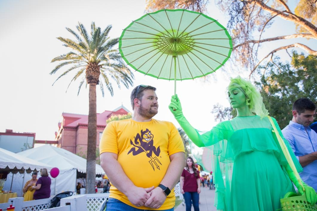 woman dressed in green costume holding umbrella over man
