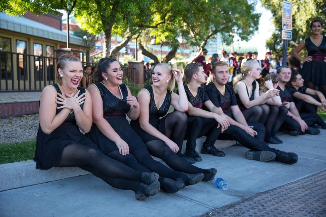 dancers sitting on sidewalk