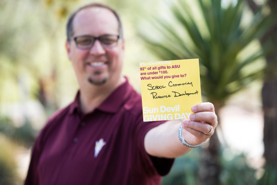 man holding post-it note saying: 92% of all gifts to ASU are under $100. What would you give to? School Community Resource Development