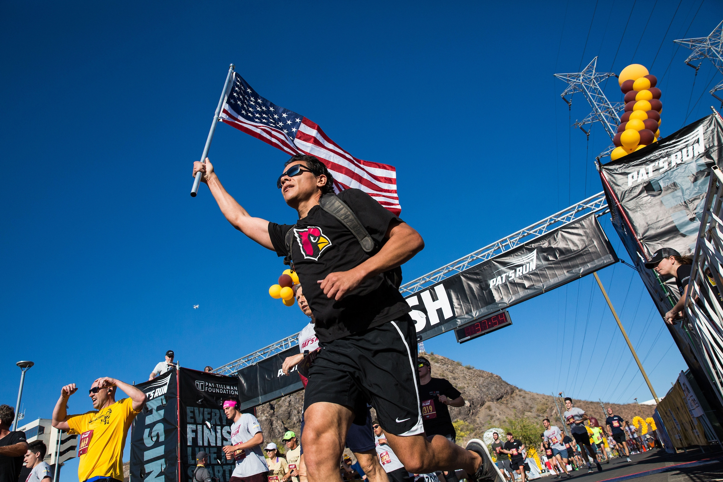 man carrying flag passing finish line in race