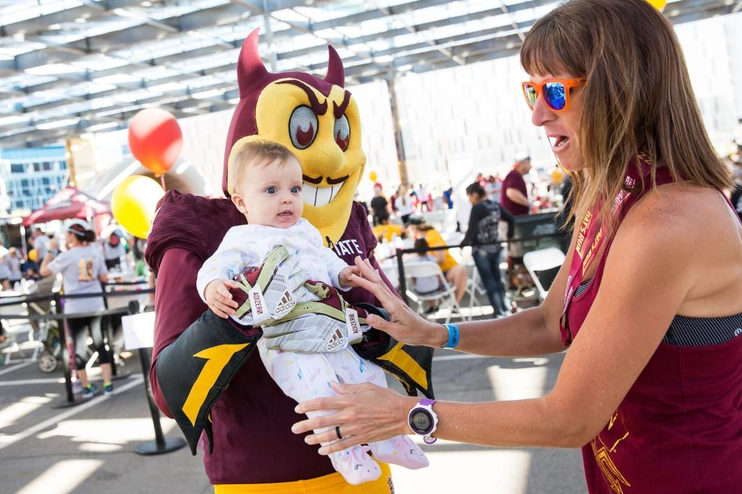 Sparky mascot holding a baby