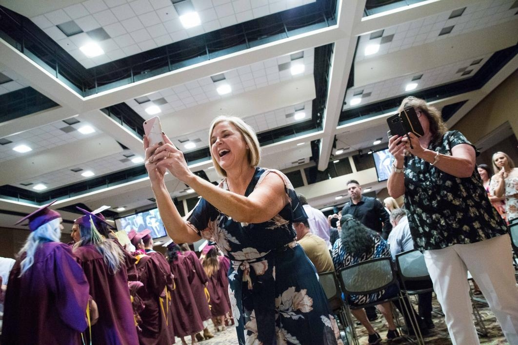 woman taking photo of daughter at graduation