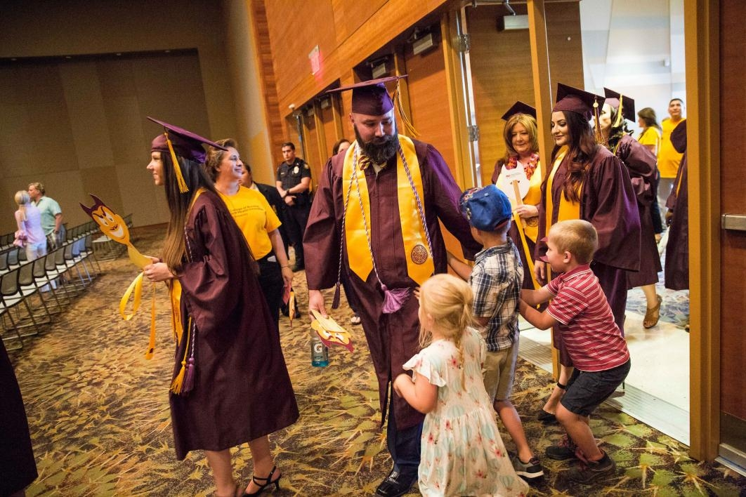 graduate high-fiving his children