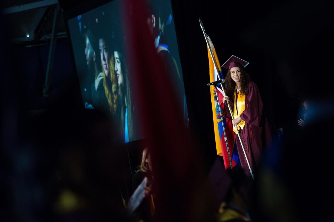 woman holding flag at graduation ceremony